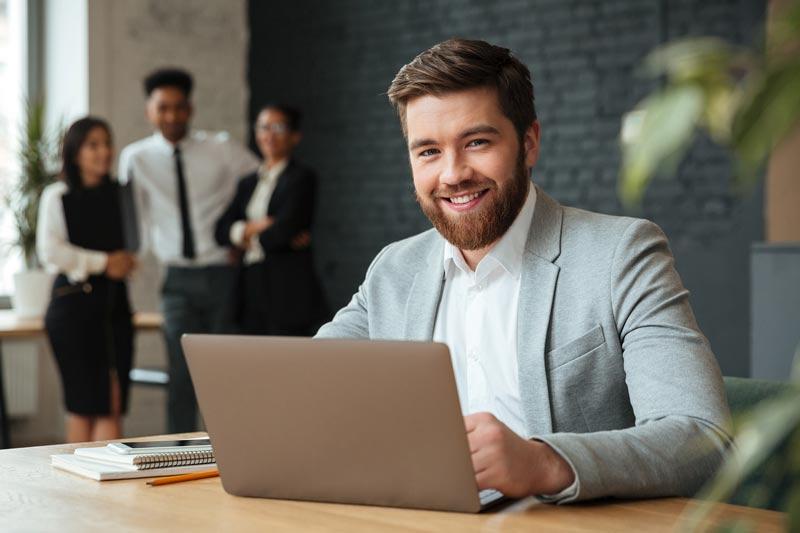 Foto hombre sonriendo en la computadora trabajando junto a Rodio Consulting